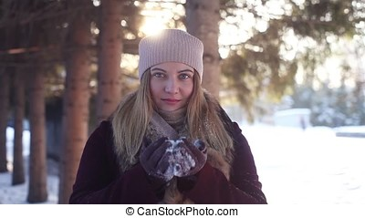 Young girl playing with snow in the woods in winter outdoors