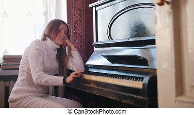 Young girl plays the piano - depressive concept, close up