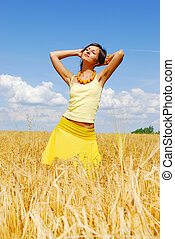 Young girl posing on plant of wheat