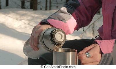 Young girl pours tea into a mug