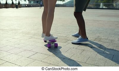 Young girl practicing skateboarding with skillful instructor