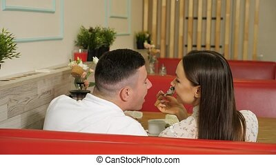 young girl pretends to feed man eating cake at table - young...