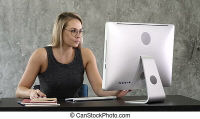 Young girl putting on glasses and starts working on the computer sitting at table.