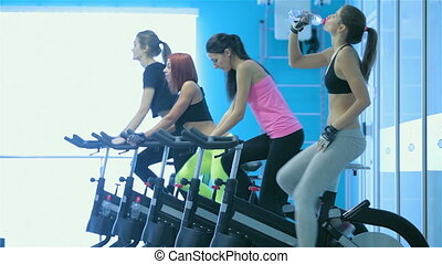 Young girl quench the thirst until her girlfriends athletes pedaling on a stationary bike
