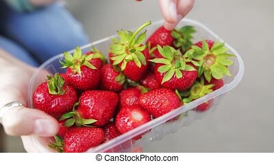 Young girl raw food shows selected berries of organic strawberries.