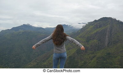 Young girl reaching up top of mountain and raised hands. Woman tourist standing on the edge of beautiful canyon, victoriously outstretching arms up. Slow motion Rear back view