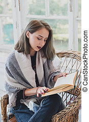 young girl reading a book in a wicker chair. Autumn mood.
