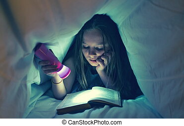 Young girl reading a book in bed