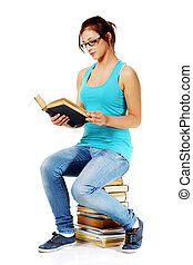 Young girl reading a book sitting on books.