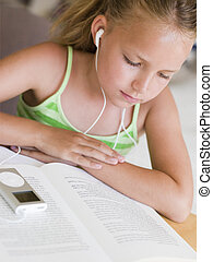 Young Girl Reading A Book While Listening To An MP3 Player