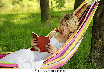Young girl reading a book while lying on a hammock