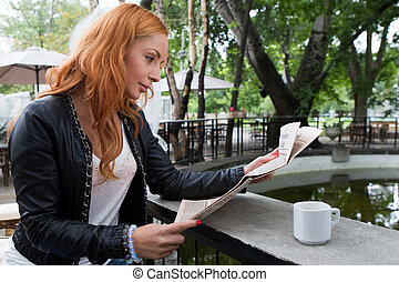 Young girl reading a newspaper in cafeteria