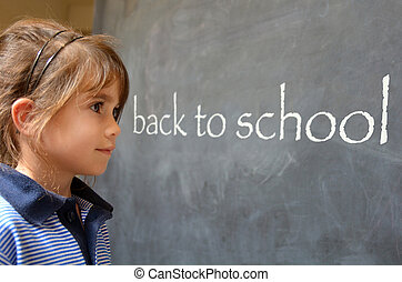Young girl reading back to school whritten on a chalkboard in a primary school
