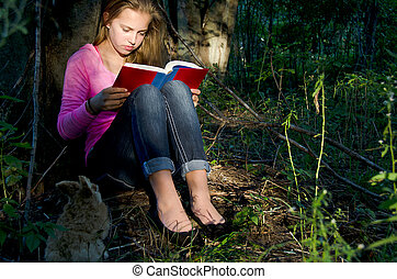 young girl reading book in forest