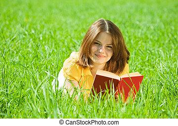 girl reading book in grass