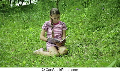 Young girl reading book in the park