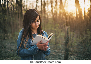 Young girl reading book outdoor