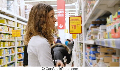 Young girl reading the labels on baby food in the store and can't choose, 4k.