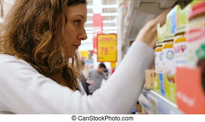 Young girl reading the labels on baby food in the store and can't choose close up, 4k.