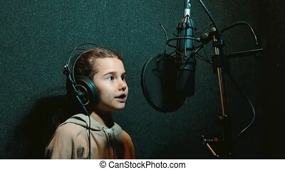 young girl recording a song in headphones in a music...