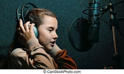 young girl recording a song in headphones in a music recording professional studio. little girl singing a song in the studio recording concept music lifestyle