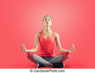 Young girl relaxing in yoga position on red background