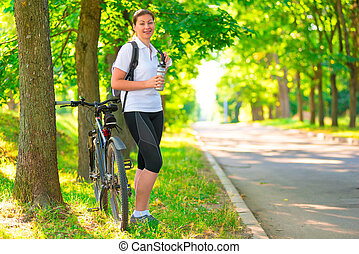 young girl resting in a park with a bicycle