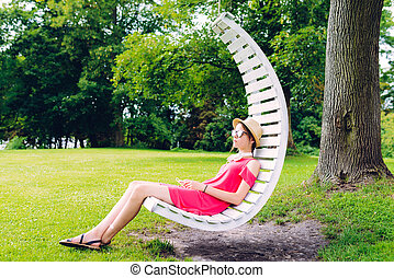girl resting on a hanging wooden chair in the garden