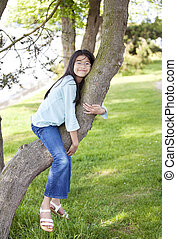 Young girl resting on a tree branch