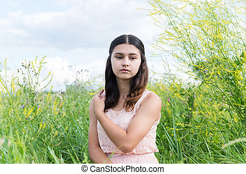 Young girl resting on meadow in summer
