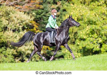 Young girl riding a black horse