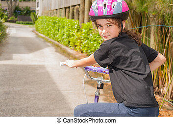 Young girl riding bicycle wearing helmet turns her head and looks back with a smila.