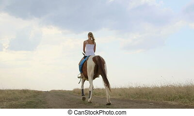 Young girl riding horse down the trail