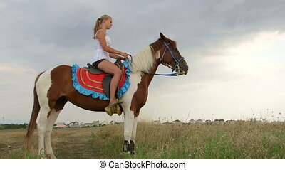 Young girl riding horse in field near the village