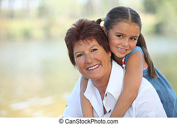 Young girl riding piggy-back on her grandmother's back