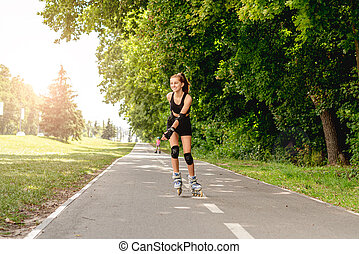Young girl roller skating in park