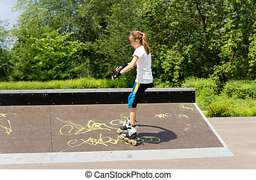 Young girl roller skating in the park
