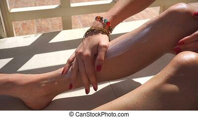 young girl rubbing sunblock on body