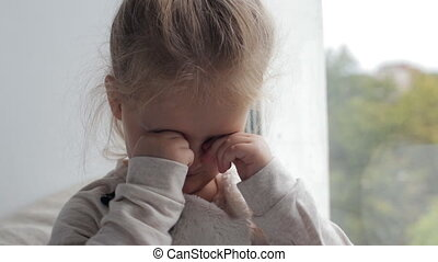 Young girl rubs her eyes sitting near the window at home