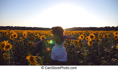 Young girl running along sunflowers field under blue sky at sunset. Sun shine at background. Follow to woman jogging at meadow and enjoying freedom. Rear back view Slow motion