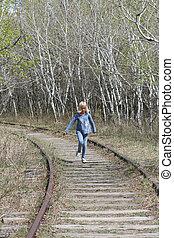 Young Girl Running Along Tracks