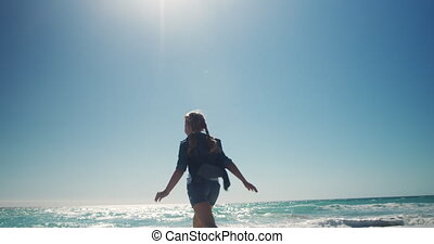 Rear view of a Caucasian girl on a sunny beach, running and jumping on sand, with blue sky and sea in the background in slow motion