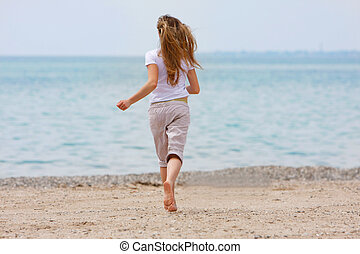 young girl running away on beach