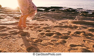 Young girl running barefoot at the sunny beach, slow motion