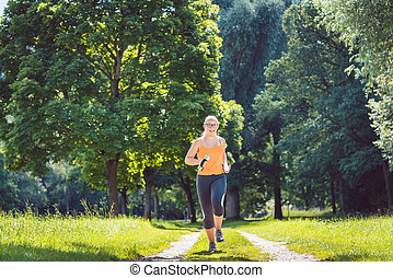 Young girl running down a path on meadow with weight dumbbells
