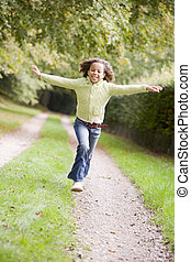 Young girl running on a path outdoors smiling