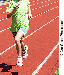 Young girl running on a red track