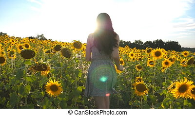 Young girl running on yellow sunflower field with sun flare...