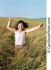 Young girl running outdoors smiling