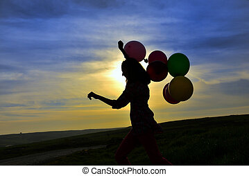 young girl running with balloons at sunset